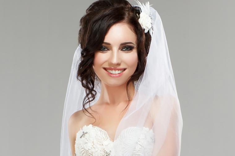 radiosa sposa con abito bianco con scollatura a cuore, velo e fiore, esempi trucco sposa