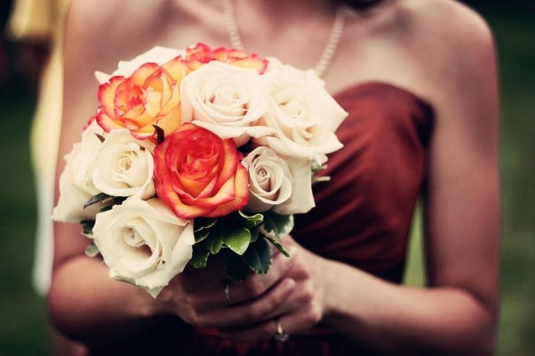 Bouquet colorato per un ospite matrimonio con un vestito rosso e collana di perle