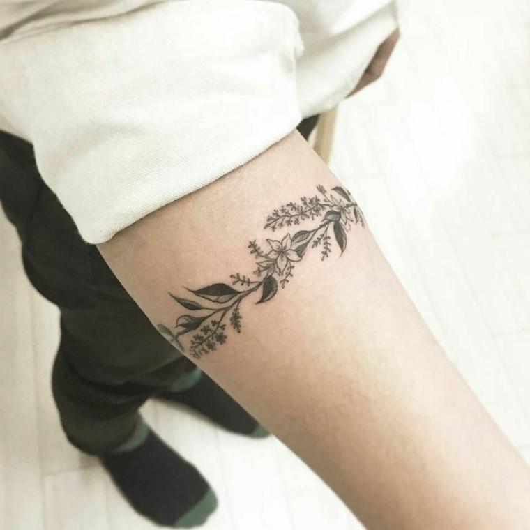delicati fiori e foglie a bracciale sul braccio di una ragazza, idea per piccoli tattoo feminili