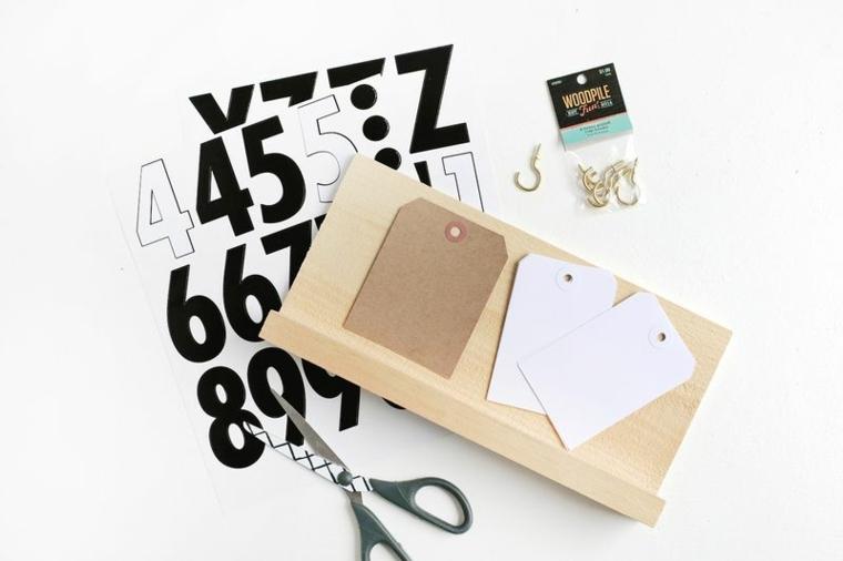 Lavoretti con la carta e un'idea con calendario fai da te con un pezzo di legno e ganci di metallo