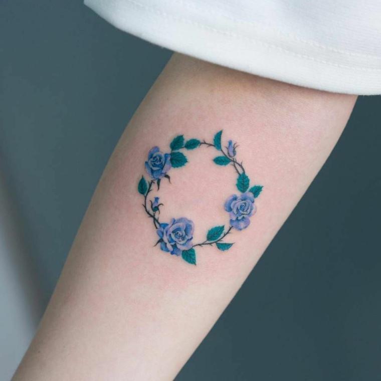 idea per un tattoo sul braccio, un cerchio realizzato con delle piccole rose blu