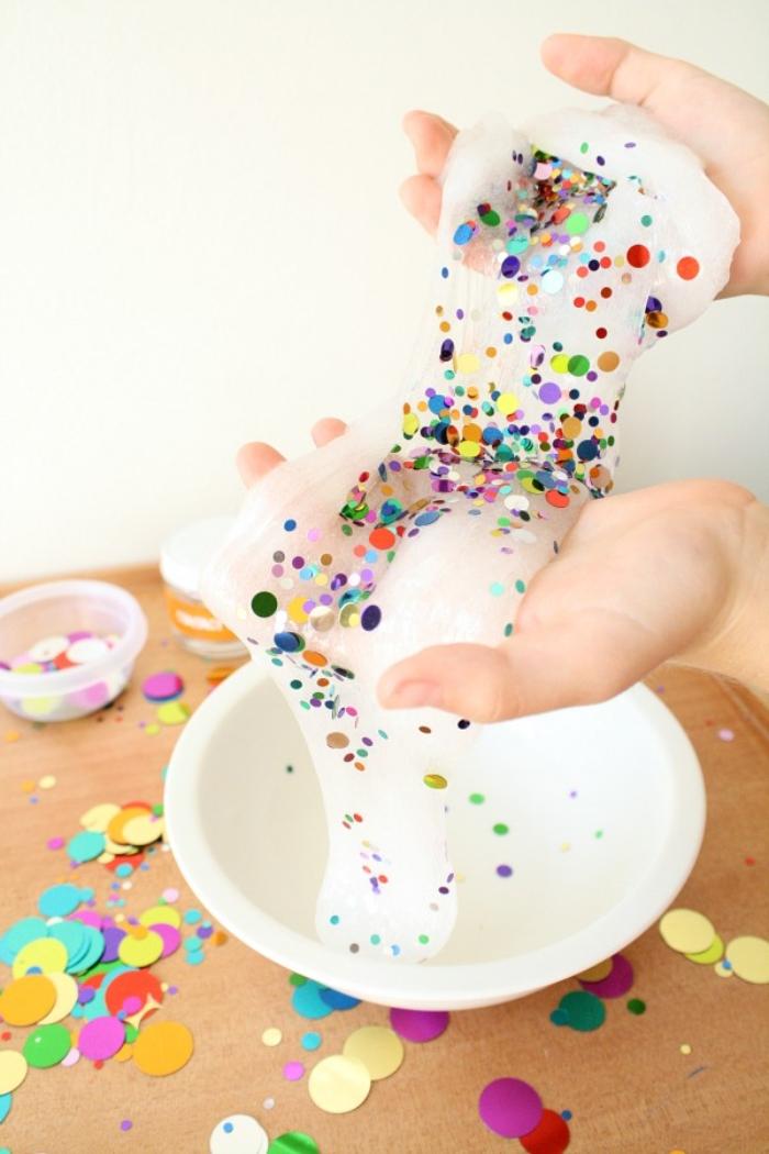 Slime fatto in casa di colore bianco con decorazione di piccoli pezzettini colorati di confetti