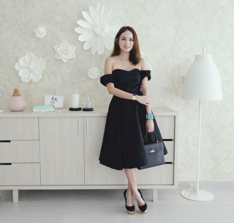 Come vestirsi ad un matrimonio, abito di colore nero con spalle scoperte e una borsetta a mano abbinata