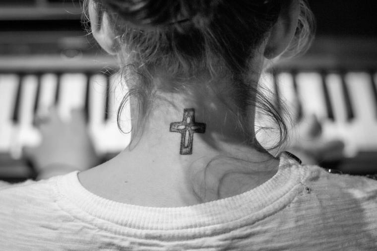 ragazza con i capelli raccolti e una maglia bianca con una croce tatuata sul collo. idee tatuaggi piccoli