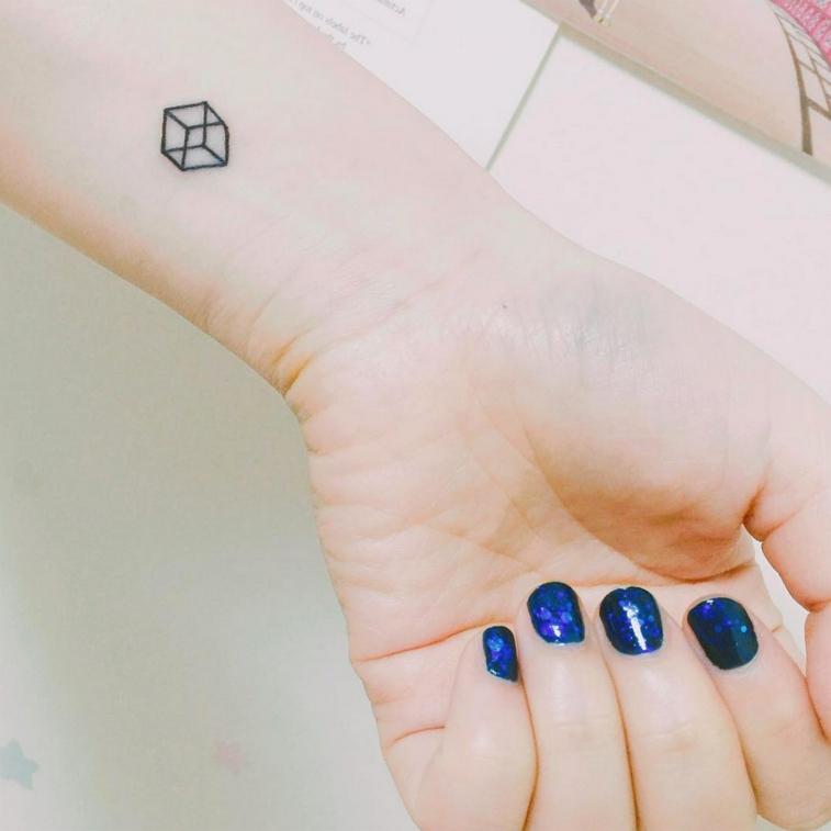 piccolo disegno tridimensionale raffigurante un cubo, idea tatuaggi al polso femminili