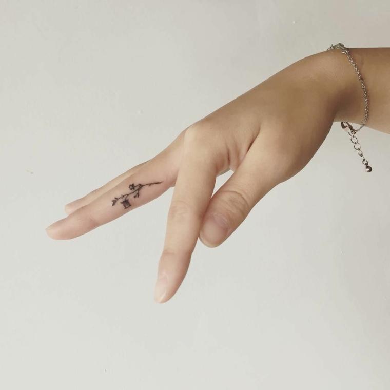 graziosa rosa piccola tatuata nella zona interna del dito medio, idea per un tattoo piccolo