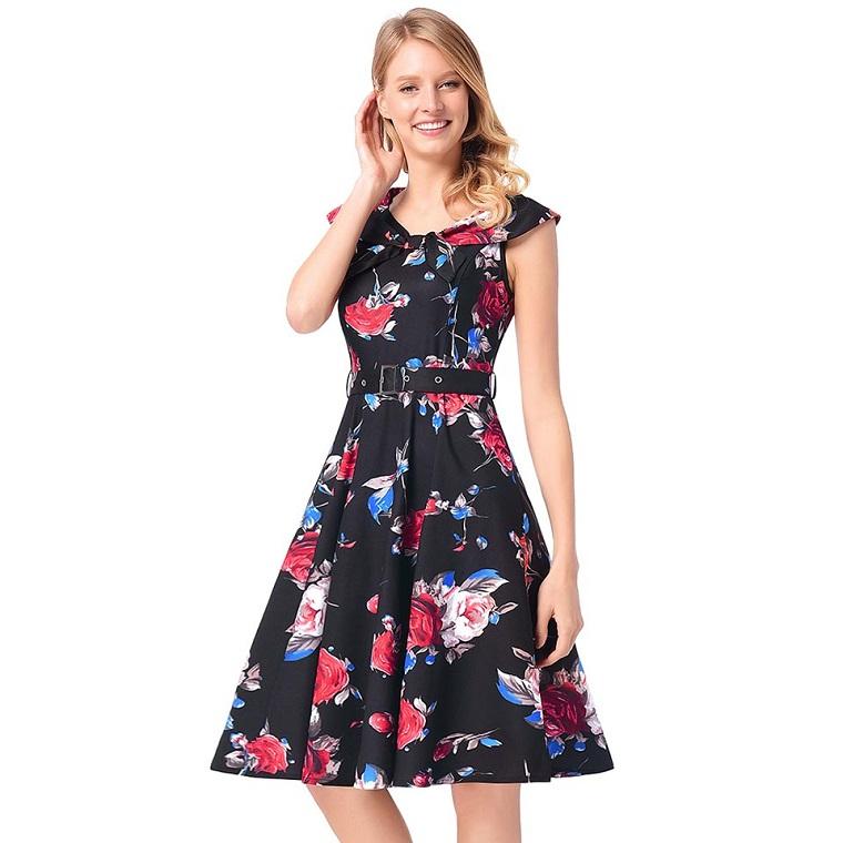 Vestito di colore nero con stampe floreali e cintura in vita, donna con i capelli biondi