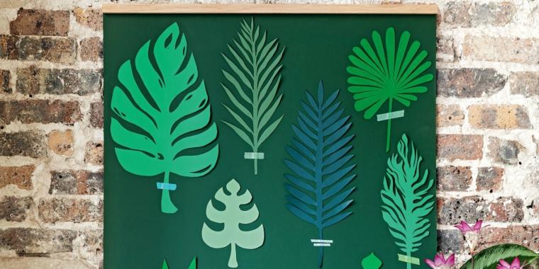 Parete con mattoni a vista e decorazione con dei lavoretti con la carta, foglie verdi di diverse piante