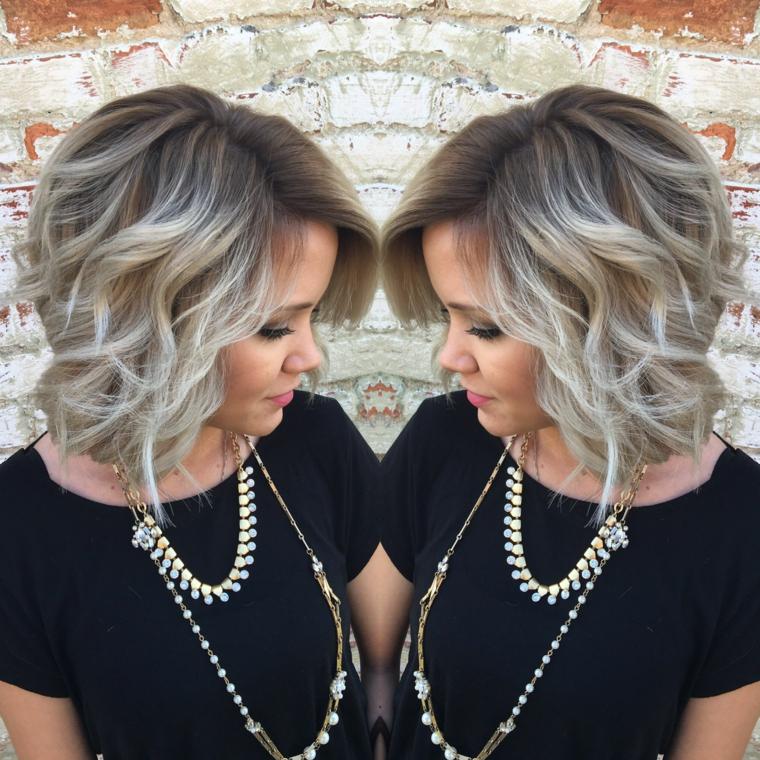 taglio di capelli corto con piega ondulata e un balayage biondo grigio, ragazza con maglia nera e collane dorate