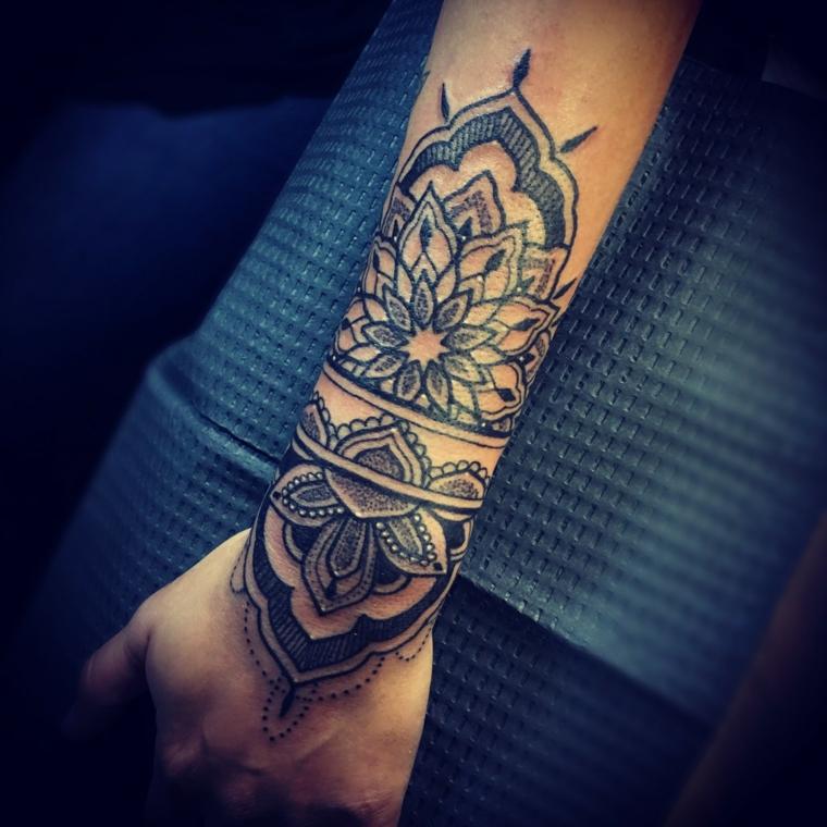 Donna con un tatuaggio fiore di loto sul braccio con tanti ornamenti e sfumature