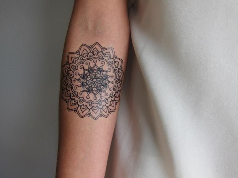 Tatuaggio simbolo forza interiore, donna con braccio tatuato simbolo mandala con tanti ornamenti