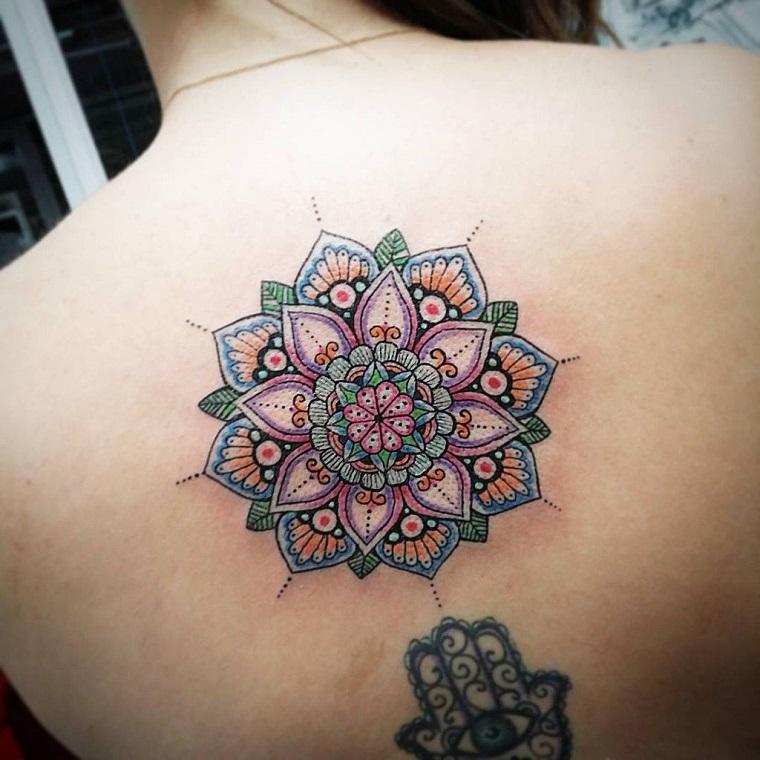 Tatuaggi mandala e un'idea per tattoo colorati sulla schiena di una ragazza