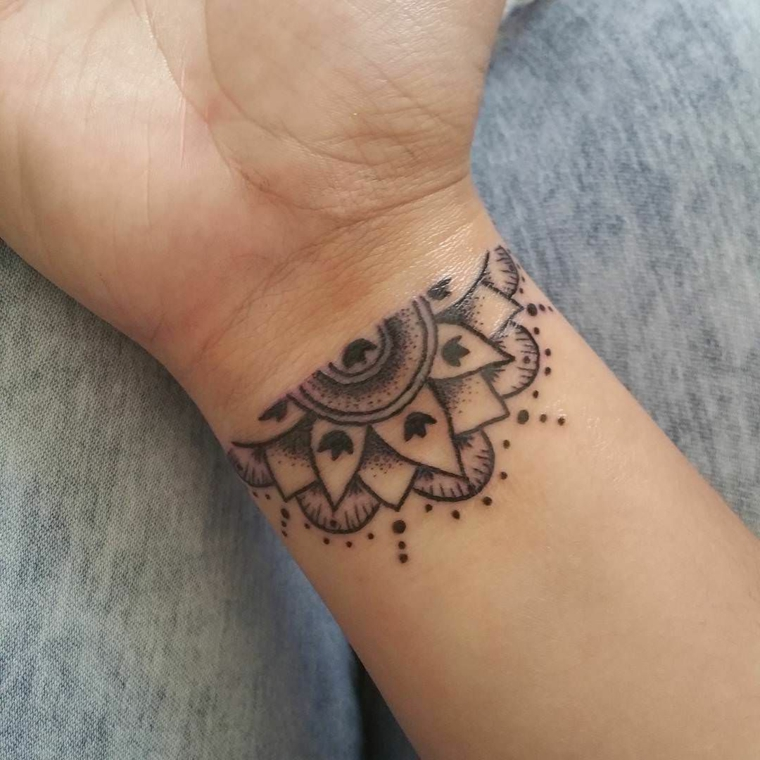 Tatuaggio simbolo forza interiore sul polso di una donna, mandala decorato con tanti puntini