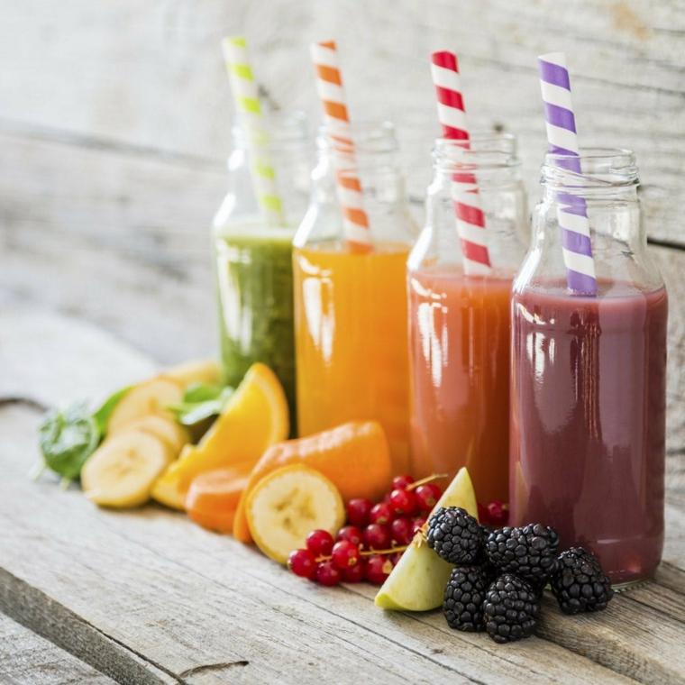Idea per conservare i frullati in delle bottiglie di vetro, frutta posizionata su un tavolo di legno