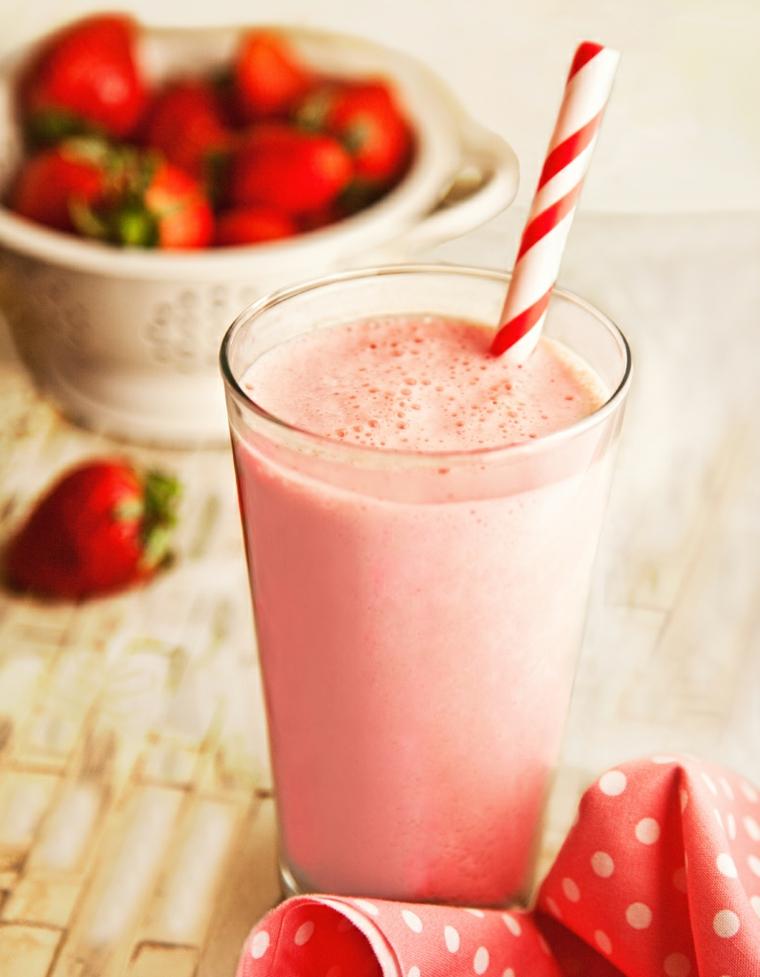 Smoothie dimagranti di fragola e latte, frullato di frutta servito in un bicchiere