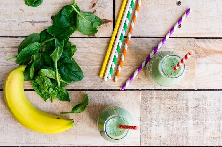 Frullati detox con fogli di spinaci e una banana servito in bottiglie di vetro con cannucce