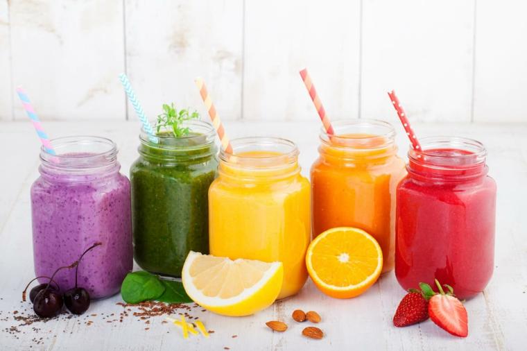 Idea per dei frullati di frutta per dimagrire, vari smoothie di agrumi serviti in barattoli di vetro