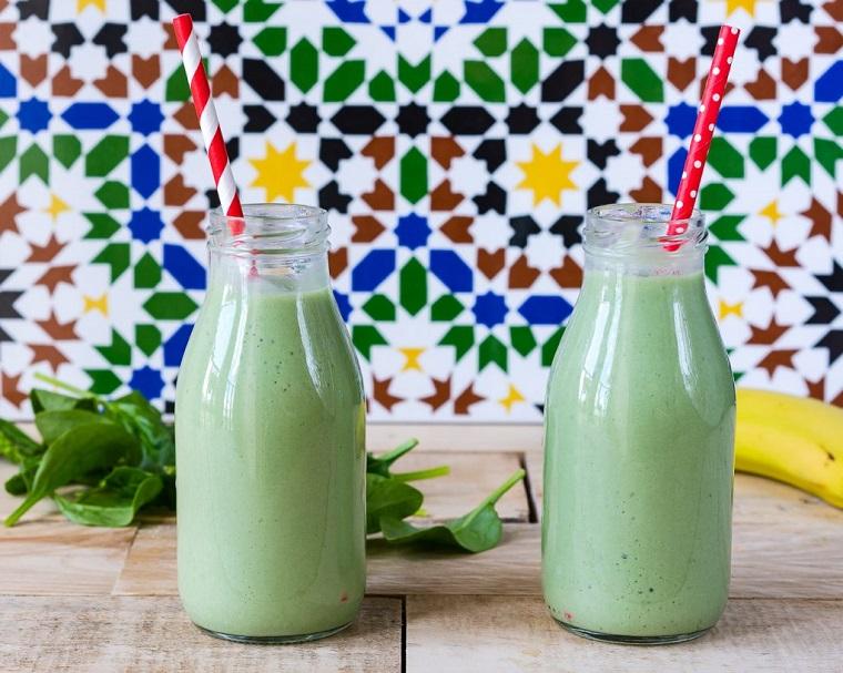 Smoothie dimagranti con spinaci e banane serviti in bottiglie di vetro