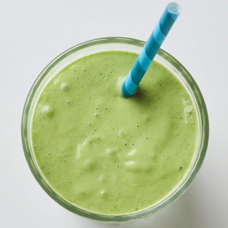 Smoothie dimagranti di colore verde e di verdura fresca in un bicchiere