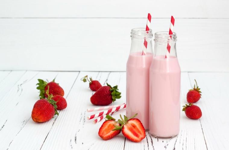 Bottiglie di vetro con frullato di fragole e latte, frutta sparsa su un tavolo