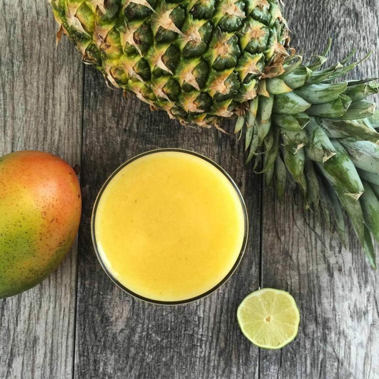 Smoothie preparato con frutta esotica come mango e ananas, aggiunta di succo di un lime