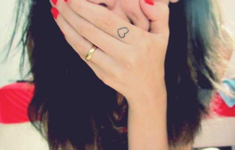 ragazza con i capelli castani e le unghie con lo smalto rosso e un grazioso esempio di tattoo piccoli donna