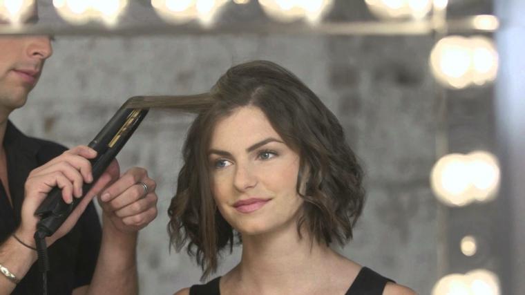 esempio capelli mossi medi come farli, ragazza con i capelli castani e un parrucchiere con la piastra