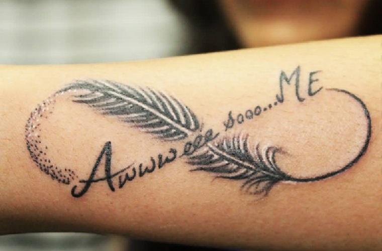 Piuma tattoo con il simbolo dell'infinito e una scritta, tatuaggio donna sul braccio