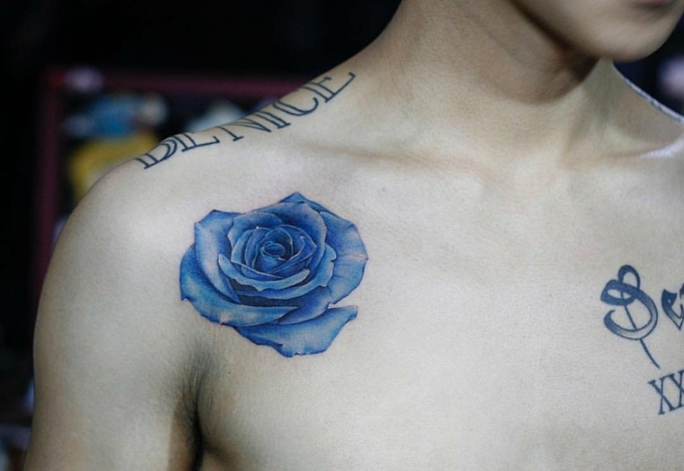 ragazzo a petto nudo con diversi tatuaggi, rosa blu sotto la scapola, significato tatuaggio rosa