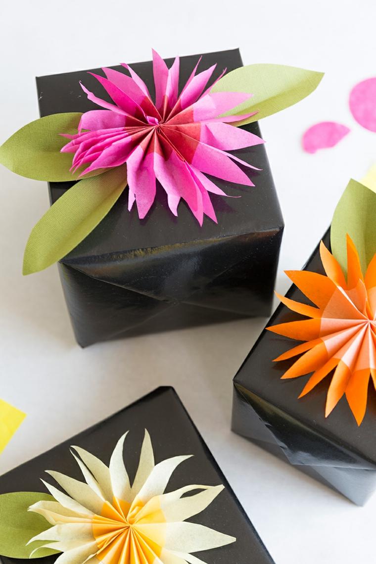 Pacchi regalo incartati con della carta nera e fiori di carta come decorazione