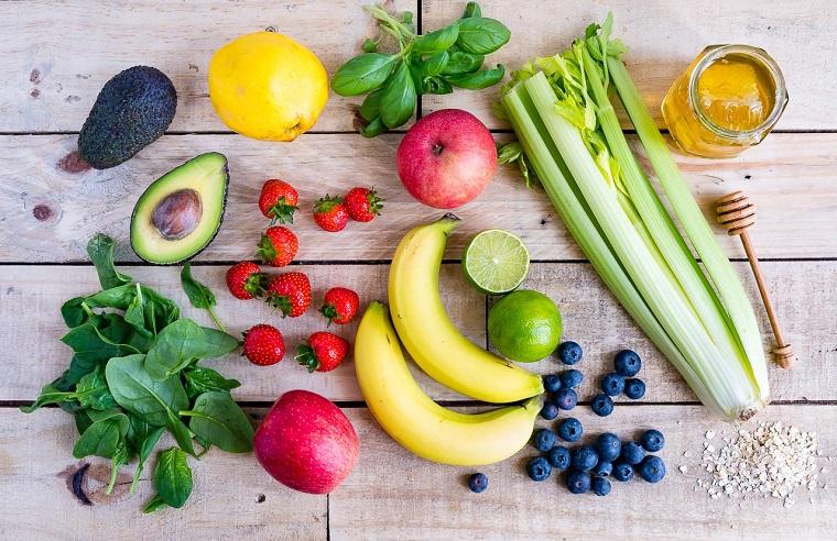 Smoothie dimagranti con frutta e verdura fresca, tanti ingredienti messi su un tavolo di legno