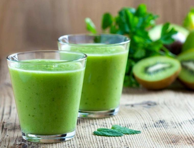 Smoothie dimagranti in bicchierini di vetro con ingredienti freschi come kiwi e insalata