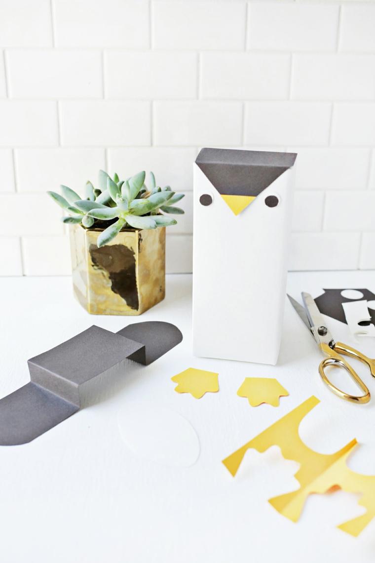 Scatola di cartone a forma di pinguino, lavoretti di carta con fogli colorati e forbici