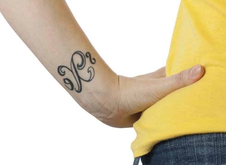 esempio per tatuaggi al polso femminili, una lettera con dei simboli su entrambi i lati