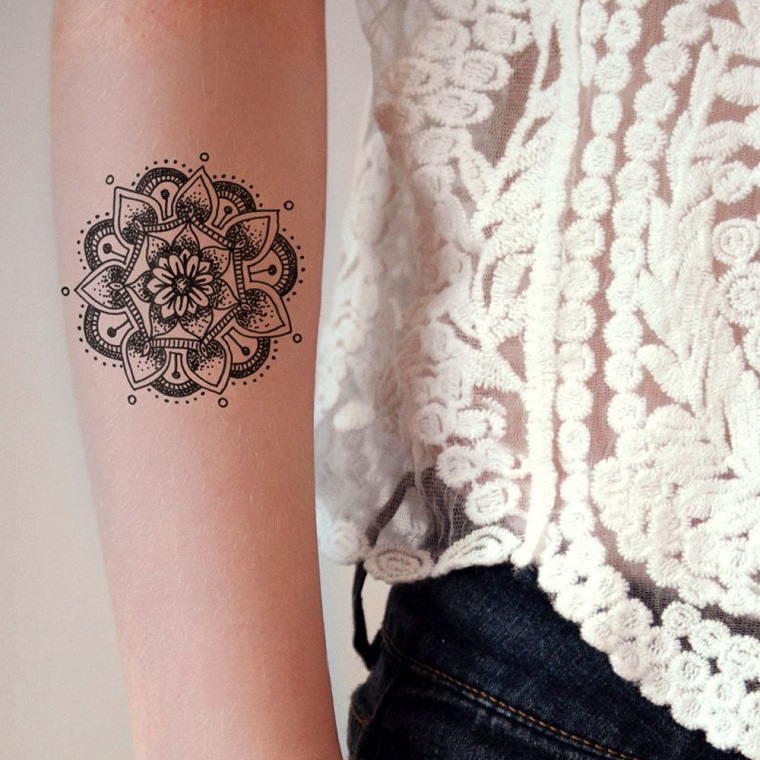 Tatuaggi mandala di media dimensione sul braccio di una donna, inchiostro di colore nero