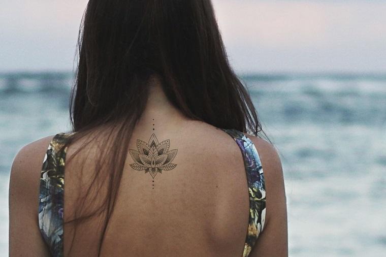 Fiore di loto tattoo sulla schiena di una ragazza con i capelli di colore castano