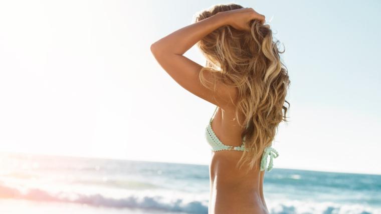 bikini in pizzo verde, onde del mare e ragazza con capelli mossi naturali biondi