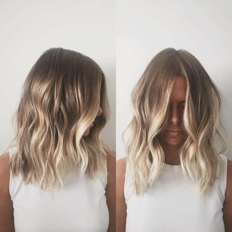 taglio di capelli di media lunghezza con piega morbida e riga in mezzo e capelli balayage biondo