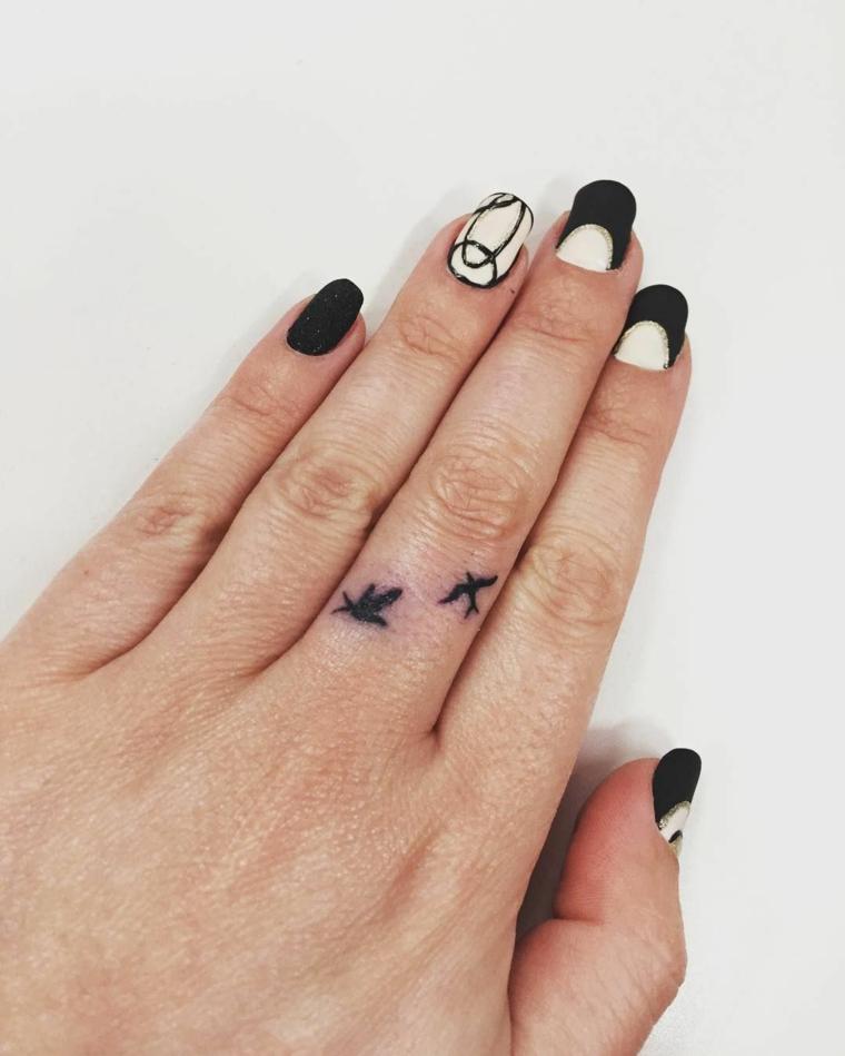 idea per tatuaggi particolari due piccole rondini nere sul dito medio di una ragazza