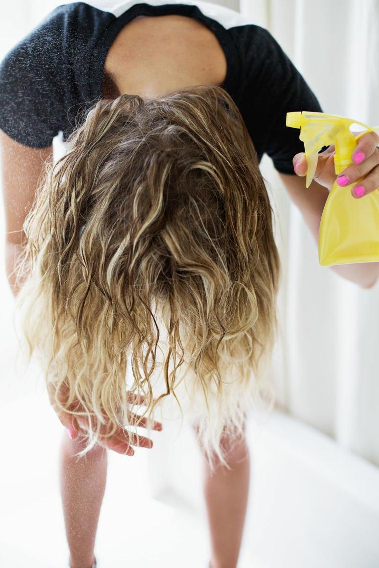 ragazza con i capelli biondi, fase per fare capelli mossi, spruzzare l'acqua con il sale