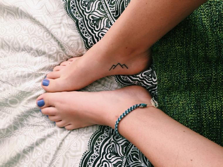 unghie del piede con lo smalto blu e tatuaggi piccoli femminili a forma di montagne