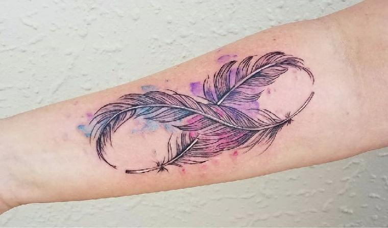 Tatuaggi femminili braccio con il simbolo dell'infinito e piuma colorata