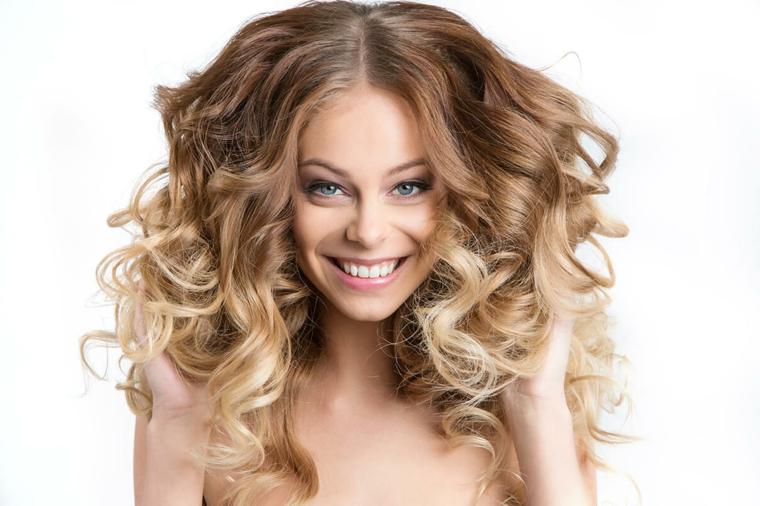 splendida ragazza sorridente con gli occhi azzurri e i capelli biondi, onde capelli come fare