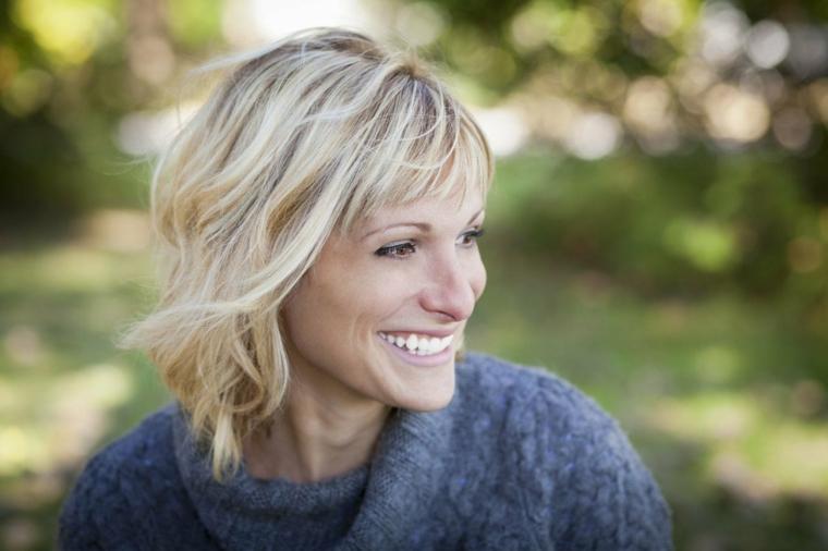 frangia e capelli corti scalati con dei balayage biondo miele di tendenza, maglione blu
