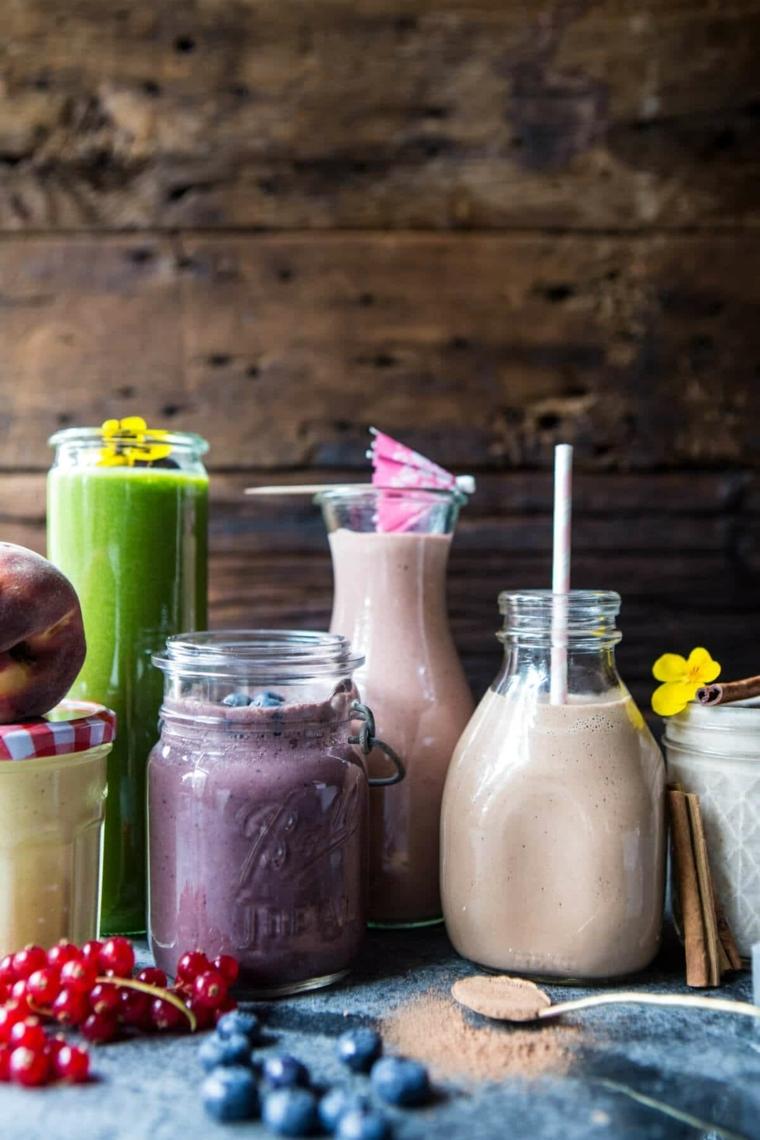 Contenitori di vetro con tanti frullati, smoothie gustosi allungati con acqua e latte