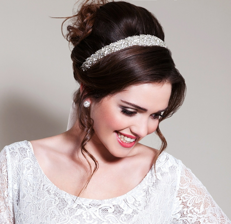 elegante abito in pizzo bianco, capelli scuri raccolti con un cerchietto di brillanti, rossetto rosso, trucco matrimonio sposa