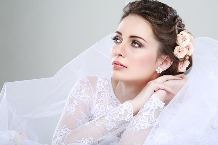 bellissima sposa con abito bianco in pizzo, rose arancioni tra i capelli. tutorial trucco sposa