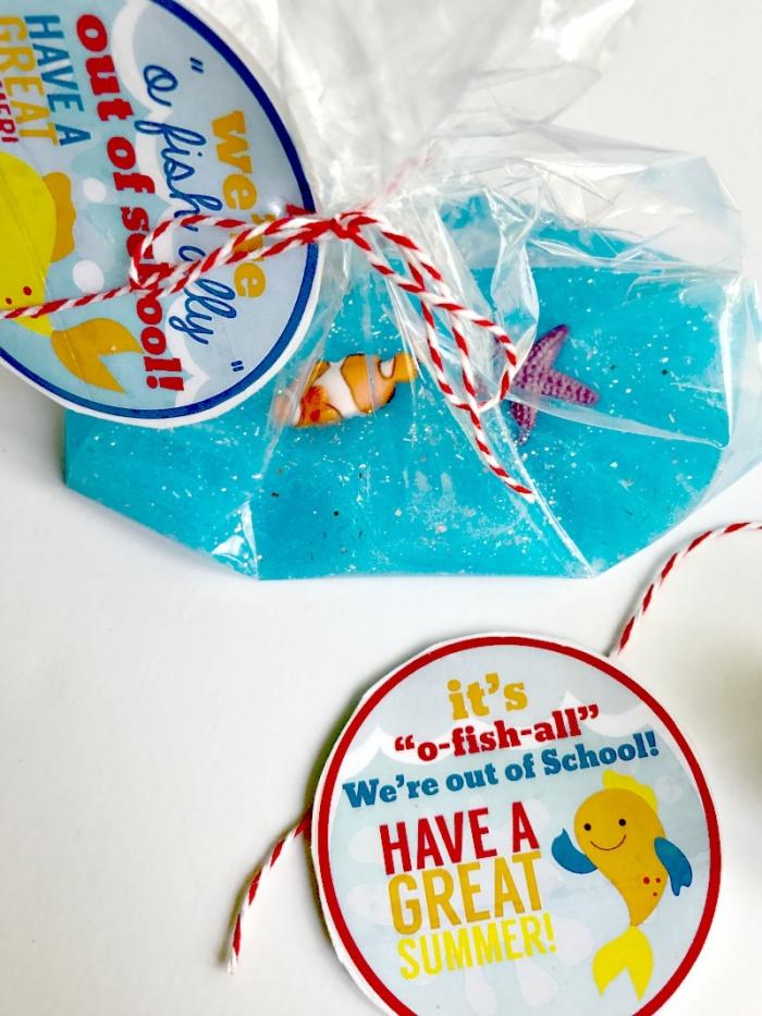 Come fare lo slime in casa di colore azzurro con glitter, sacchetto con pasta di melma e pesciolini