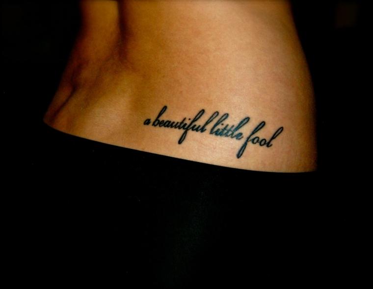 idea per tatuaggi eleganti una scritta in corsivo sull'anca di una ragazza con la gonna nera