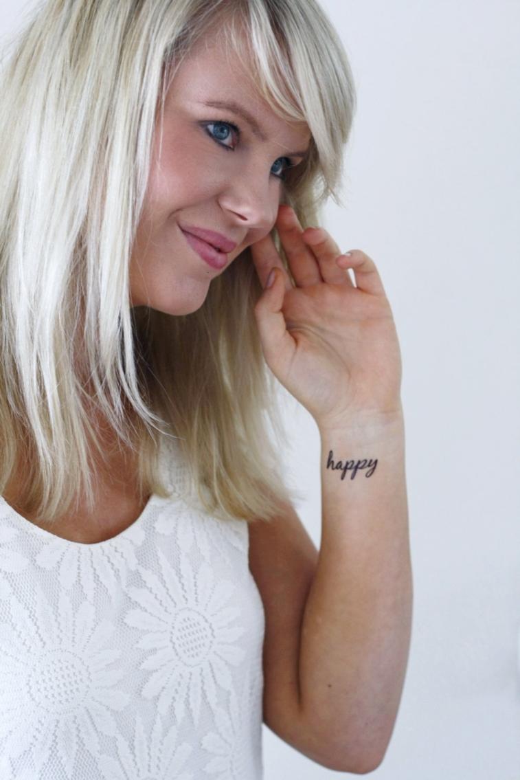 ragazza con i capelli biondi lisci e gli occhi azzurri con una scritta tatuaggi al polso femminili